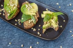 Avocado sandwich with basil and sprouts of green buckwheat on a. Black straight-headed plate, bitten off piece, dark blue background. Healthy vegan food concept Stock Image