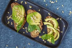 Avocado sandwich with basil and sprouts of green buckwheat on a. Black straight-headed plate, dark blue background. Healthy vegan food concept Royalty Free Stock Photography