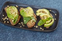 Avocado sandwich with basil and sprouts of green buckwheat on a. Black straight-headed plate, dark blue background. Healthy vegan food concept Royalty Free Stock Photo