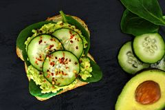 Avocado sandwich with cucumber and spinach on dark slate background Royalty Free Stock Photos