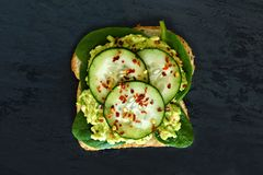 Avocado sandwich with cucumber and spinach on dark slate Stock Photos