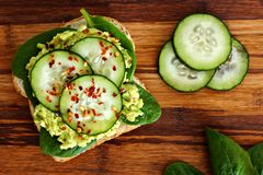 Avocado sandwich with cucumber and spinach over wood Stock Photo