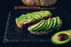 Avocado sandwich on dark rye bread made with fresh sliced avocados from above Royalty Free Stock Photo