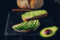 Avocado sandwich on dark rye bread made with fresh sliced avocados from above Stock Photos