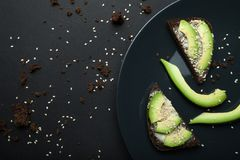 Avocado sandwich on dark rye bread, made from fresh sliced avocado with melted cheese and sesame. Top view on a black plate. The royalty free stock photo