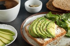 Avocado sandwich on dark rye toast bread. Made with fresh sliced avocado, cream cheese and seeds, from above Royalty Free Stock Photos