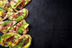 Avocado sandwich on homemade ciabatta bread made with fresh sliced avocados and fried crispy bacon from above. Top view image. Cop. Yspace for your text Royalty Free Stock Image