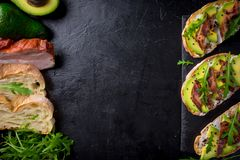 Avocado sandwich on homemade ciabatta bread made with fresh sliced avocados and fried crispy bacon from above. Top view image. Cop. Yspace for your text Stock Photo
