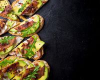 Avocado sandwich on homemade ciabatta bread made with fresh sliced avocados and fried crispy bacon from above. Top view image. Cop. Yspace for your text Stock Photos
