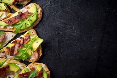 Avocado sandwich on homemade ciabatta bread made with fresh sliced avocados and fried crispy bacon from above. Top view image. Cop. Yspace for your text Royalty Free Stock Photo