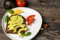 Avocado sandwich with walnuts, tomato and lemon on a white plate and wooden table. Avocado sandwich with slices of avocado with tomato and basil leaves on the royalty free stock photography