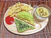 Avocado sandwiches and potatoes with kiwi yogurt. Avocado splash sandwiches and potatoes with kiwi yogurt stock images