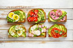 Avocado sandwiches, toasts with various vegetarian toppings on a white wooden table. Top view Royalty Free Stock Image