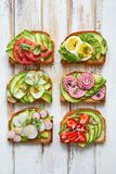 Avocado sandwiches, toasts with various vegetarian toppings on a white wooden table. Top view Stock Image