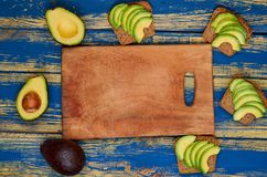 Avocado sandwiches on the wooden board with copy space for text. Healthy vegan diet breakfast. Top view royalty free stock images