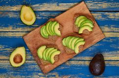 Avocado sandwiches on the wooden board. Healthy vegan diet breakfast concept. Top view stock images