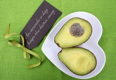 Avocado schnitt zur Hälfte auf Herzformplatte Stockfotos