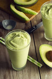 Avocado Shake or Smoothie Being Poured Into Glasses. Avocado shake or smoothie is being poured into two glasses. This sweet drink is made from avocados blended Stock Photography