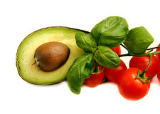 Avocado. Sliced in half with brown stone, green Basil leaves, small red tomatoes on the green line, white background, isolated Royalty Free Stock Photo