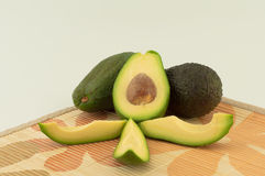 Avocado. Sliced avocado and two whole fruit on a light background stock image