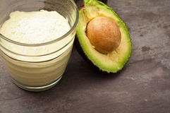 Avocado smoothie. Healthy avocado and cashew nut smoothie milkshake topped with coconut. Served on a gray stone slate background Royalty Free Stock Photos