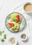Avocado, soft cheese, cherry tomatoes sandwich and tea with milk on a light background, top view. Healthy snack. Breakfast stock image