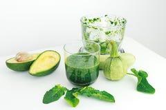 Avocado, spinaci, zucchini e miscelatore su fondo bianco Fotografia Stock