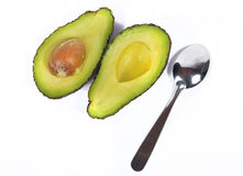 Avocado with spoon Stock Images