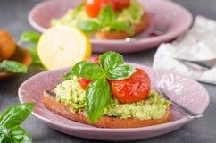 Avocado spread bread with baked tomato Royalty Free Stock Photos