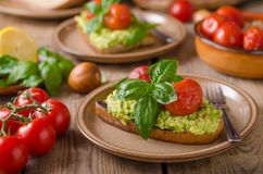 Avocado spread bread with baked tomato. Salad, fresh basil Royalty Free Stock Image