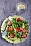 Avocado, strawberry and arugula salad. In green plate on the wooden table Royalty Free Stock Photo