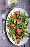 Avocado, strawberry and arugula salad with poppy seed sauce. Avocado, strawberry and arugula salad in oval white plate on the wooden table Stock Photography