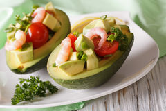 Avocado stuffed with shrimp close-up on a plate. horizontal Royalty Free Stock Photo