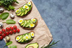 Avocado summer sandwich toast recipe with guacamole, spinach, arugula and quail eggs on parchment paper on a concrete Stock Photos