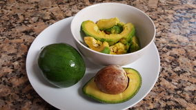 Avocado in three ways. Cultivated in tropical and mediterranean climates. now  present in tree forms ., whole. half with seeds and pulp Royalty Free Stock Images