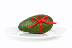 Avocado tied with a red bow Royalty Free Stock Photos