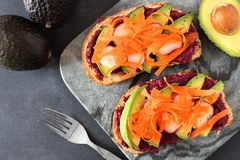 Avocado toast with beet hummus, radishes and carrots, above scene. On a dark background Royalty Free Stock Photography