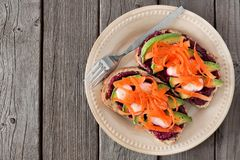 Avocado toast with beet hummus, radishes and carrots over rustic wood. Avocado toast with beet hummus, radishes and carrots, top view in a plate over rustic old Stock Photo