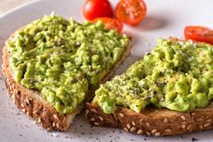 Avocado Toast. Close up of a slice of delicious avocado toast with sliced tomato stock images