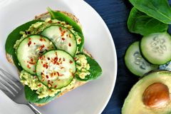 Avocado toast with cucumber and spinach on white plate Stock Images