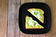 Avocado toast with egg and pea shoots on black plate Royalty Free Stock Photo
