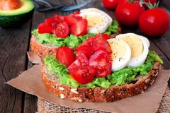 Avocado toast with eggs and tomatoes, close up on wood Royalty Free Stock Photography