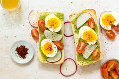 Avocado toast with eggs and tomatos Stock Photo