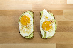 Avocado toast and fried egg on wooden background for breakfast Royalty Free Stock Photos
