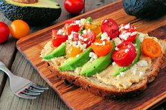 Avocado toast with hummus and tomatoes, close up on wood Stock Photo