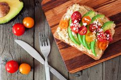 Avocado toast with hummus and tomatoes on server, above scene on wood stock photo