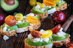Avocado Toast with Avocado Tomatoes Basil and Feta Cheese. Avocado toast sandwich with avocados, fresh from the garden heirloom tomatoes and feta cheese, Greek royalty free stock images