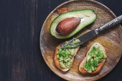 Avocado with toast served on a wooden plate. View from above.