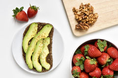 Avocado toast, walnuts and strawberries. High-angle shot of an avocado toast in a white plate, a white bowl full of strawberries and some peeled walnuts on a Stock Photos