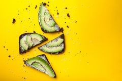 Avocado toast on a yellow background, black bread and slices of ripe avocado with cheese royalty free stock images